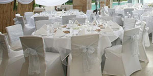 Reception venue with white ribbon chairs
